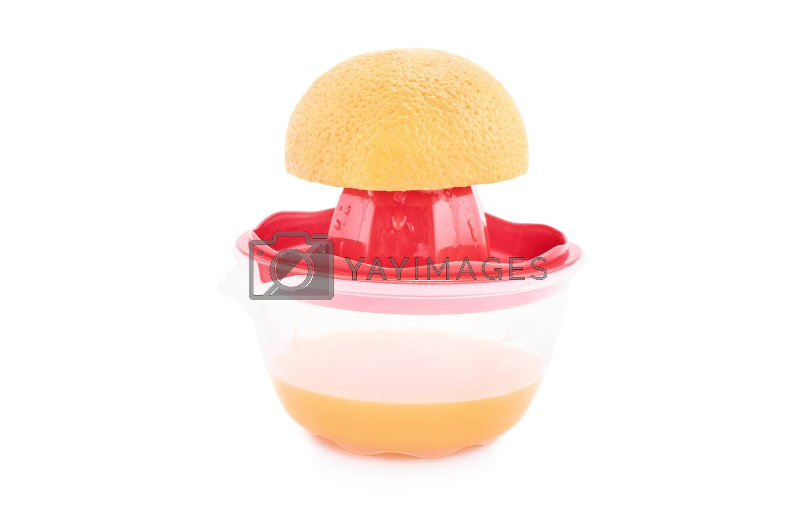 Half filled squeezer with an orange on top, isolated on white background. Making a fresh orange juice.