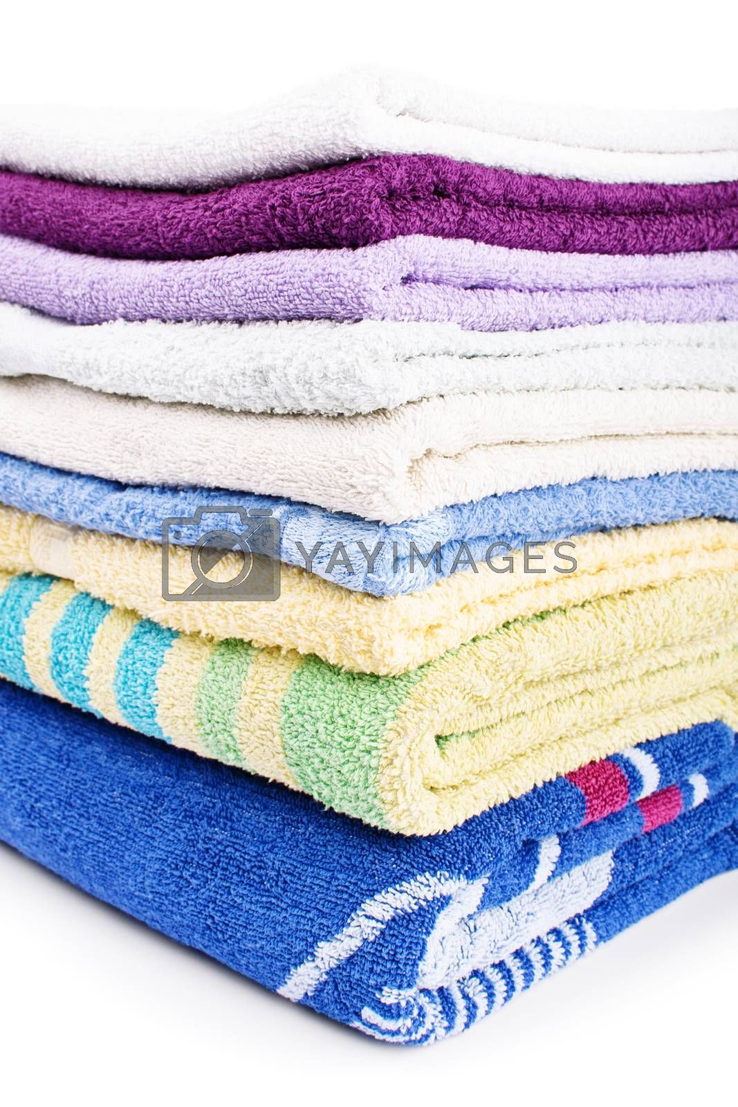 Close up shot of a pile of colorful clean bathroom towels, isolated on white background.