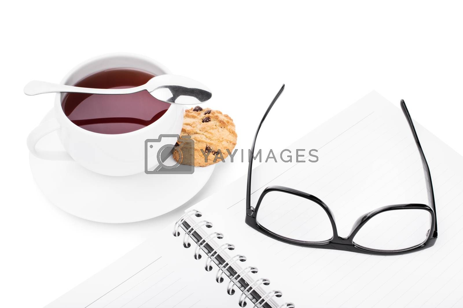 Glasses and notebook with a cup of tea and cookie, isolated on white background.