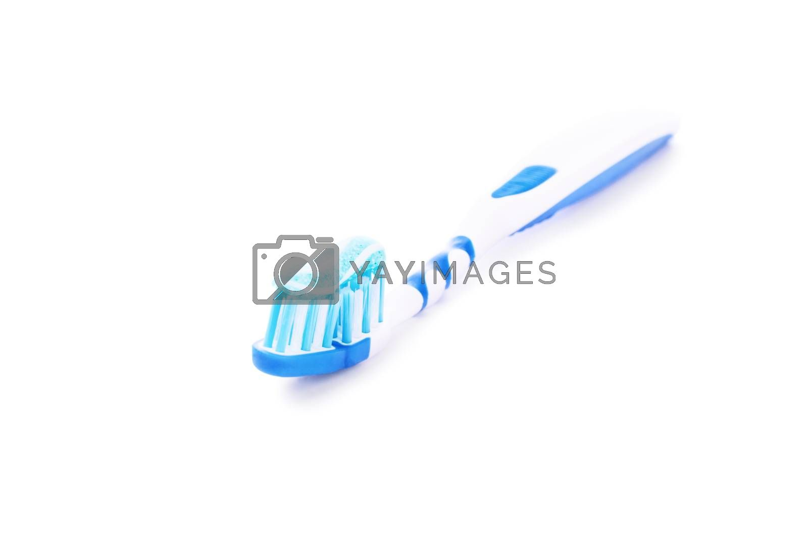 Close-up shot of a toothpaste on a blue toothbrush, isolated on white background.