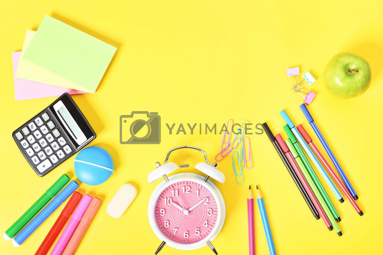 Fun school stationary scattered at the bottom on yellow background.