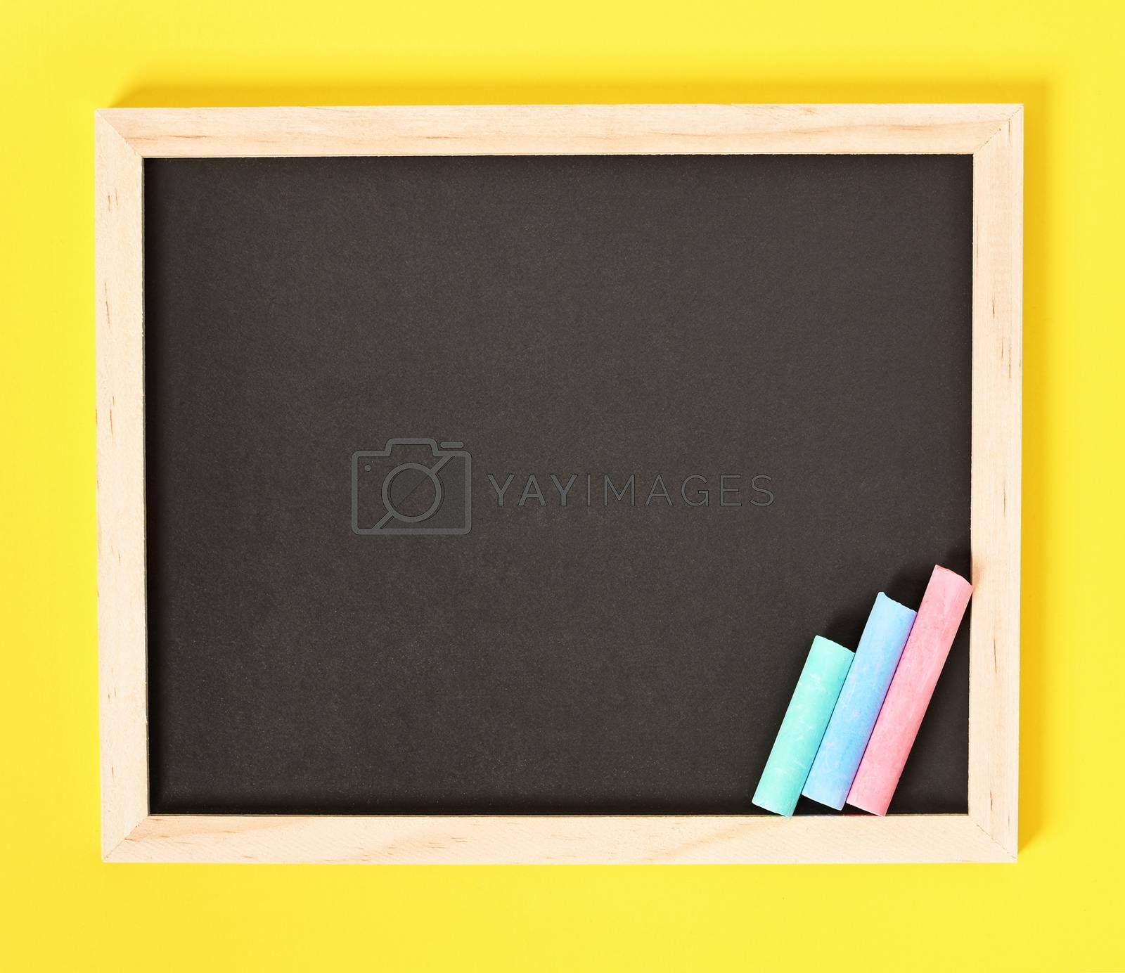Chalkboard with wooden frame and colorful chalks on one side, isolated on yellow background.