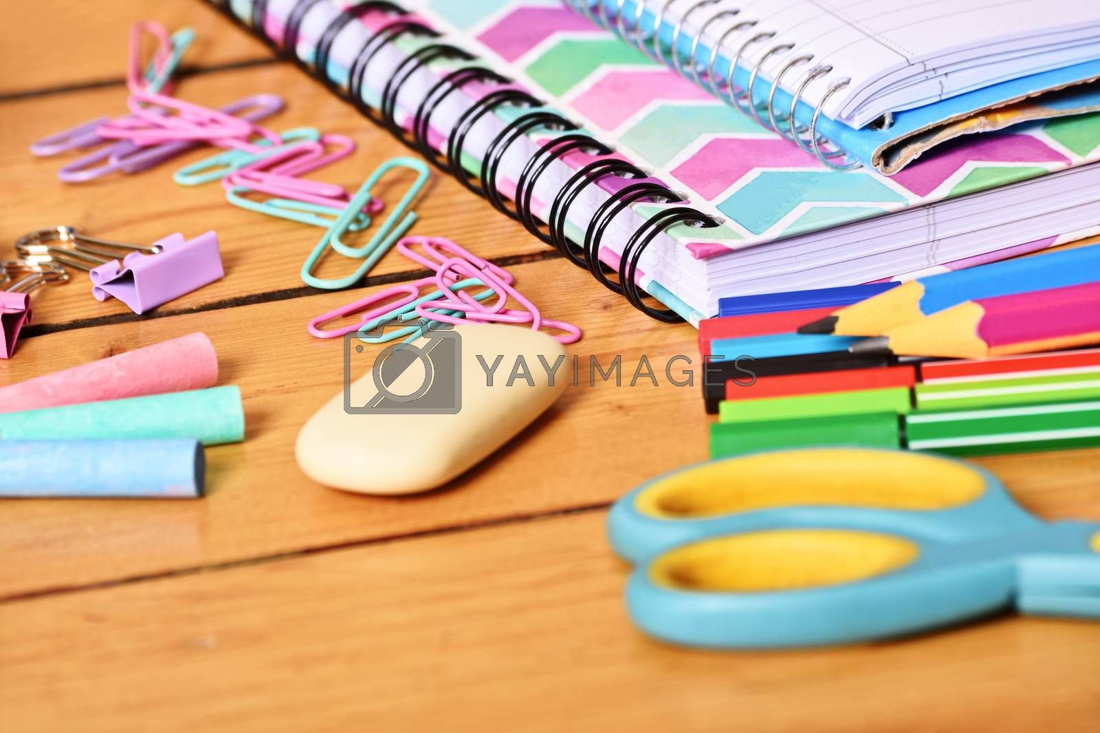 Close up shot of pastel colored girl school stationary on wooden background.