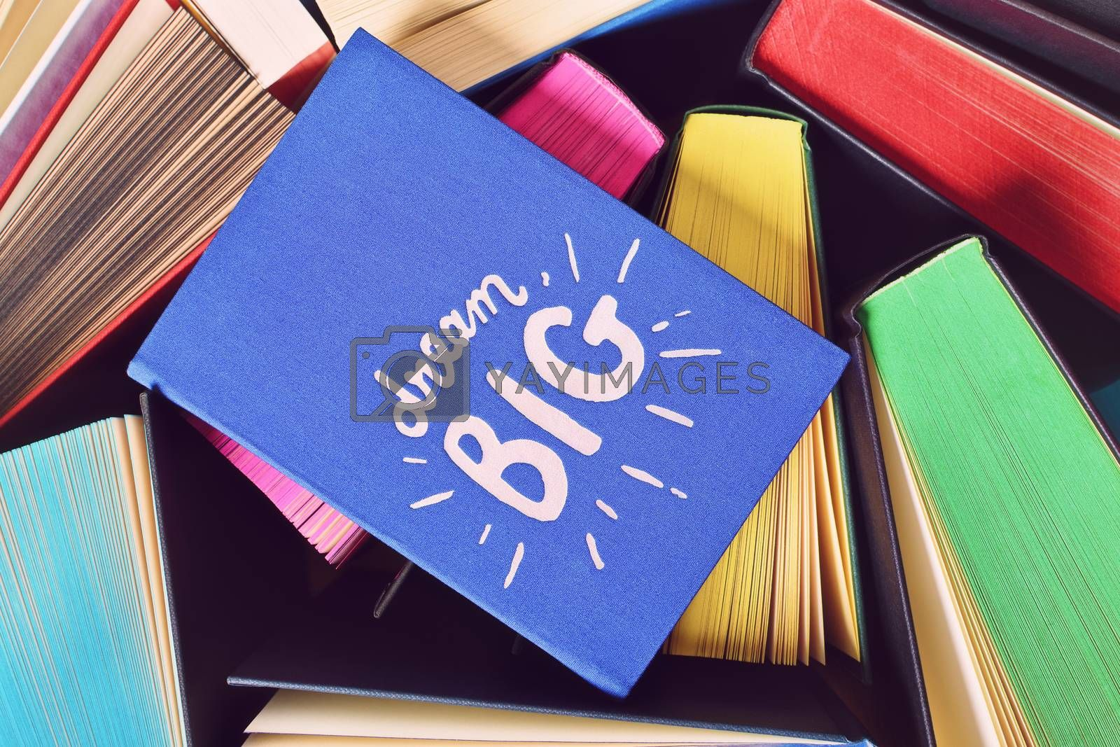 """Close up shot of a blue notebook with inspirational """"dream big"""" sign, on top of open books with multicolored sprayed edges."""