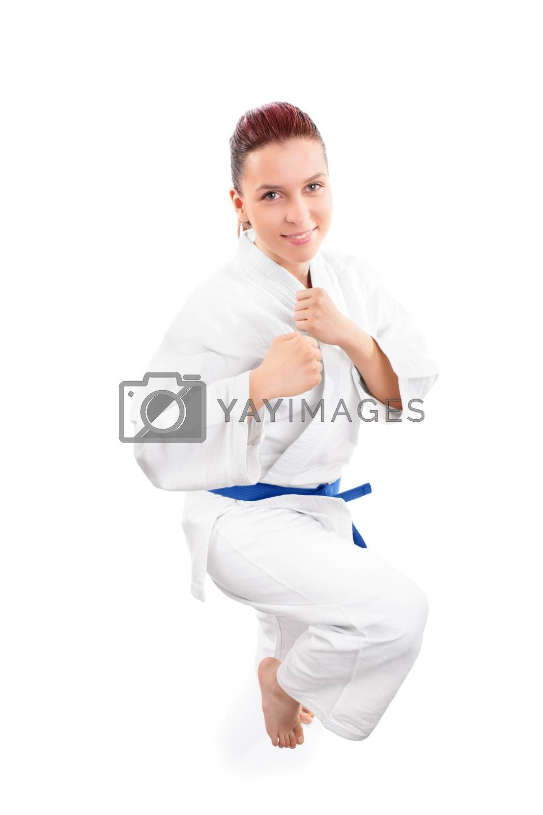 Top view of a beautiful young smiling girl in a kimono with blue belt with a raised knee preparing for a kick, isolated on white background.