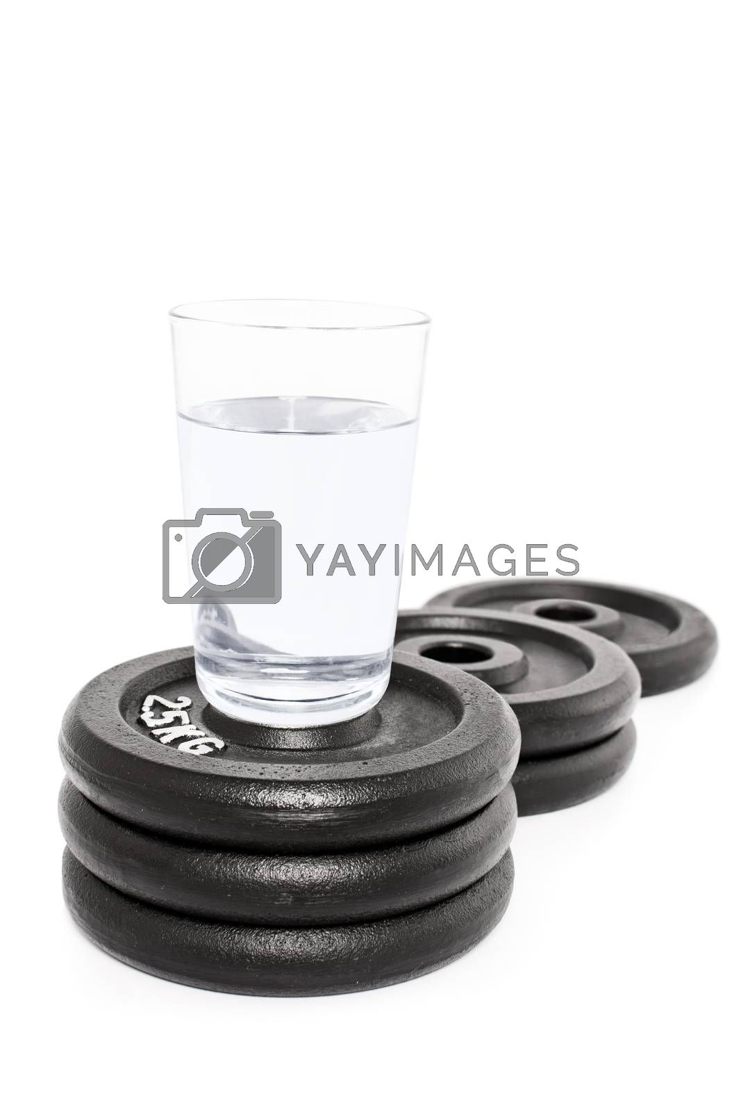 Glass of water put on a podium of weight plates, isolated on white background.