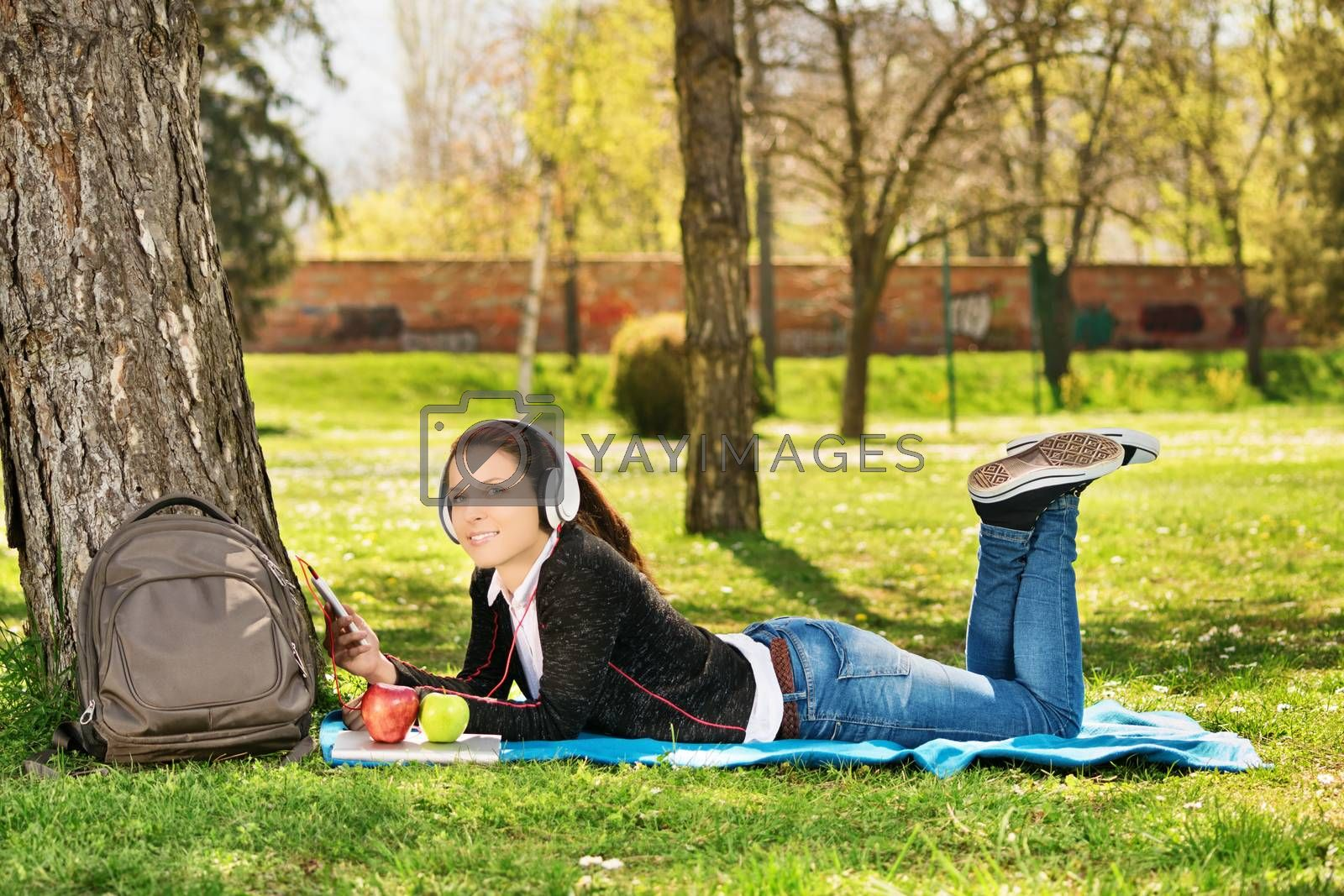 Beautiful female student listening music in the park by Mendelex