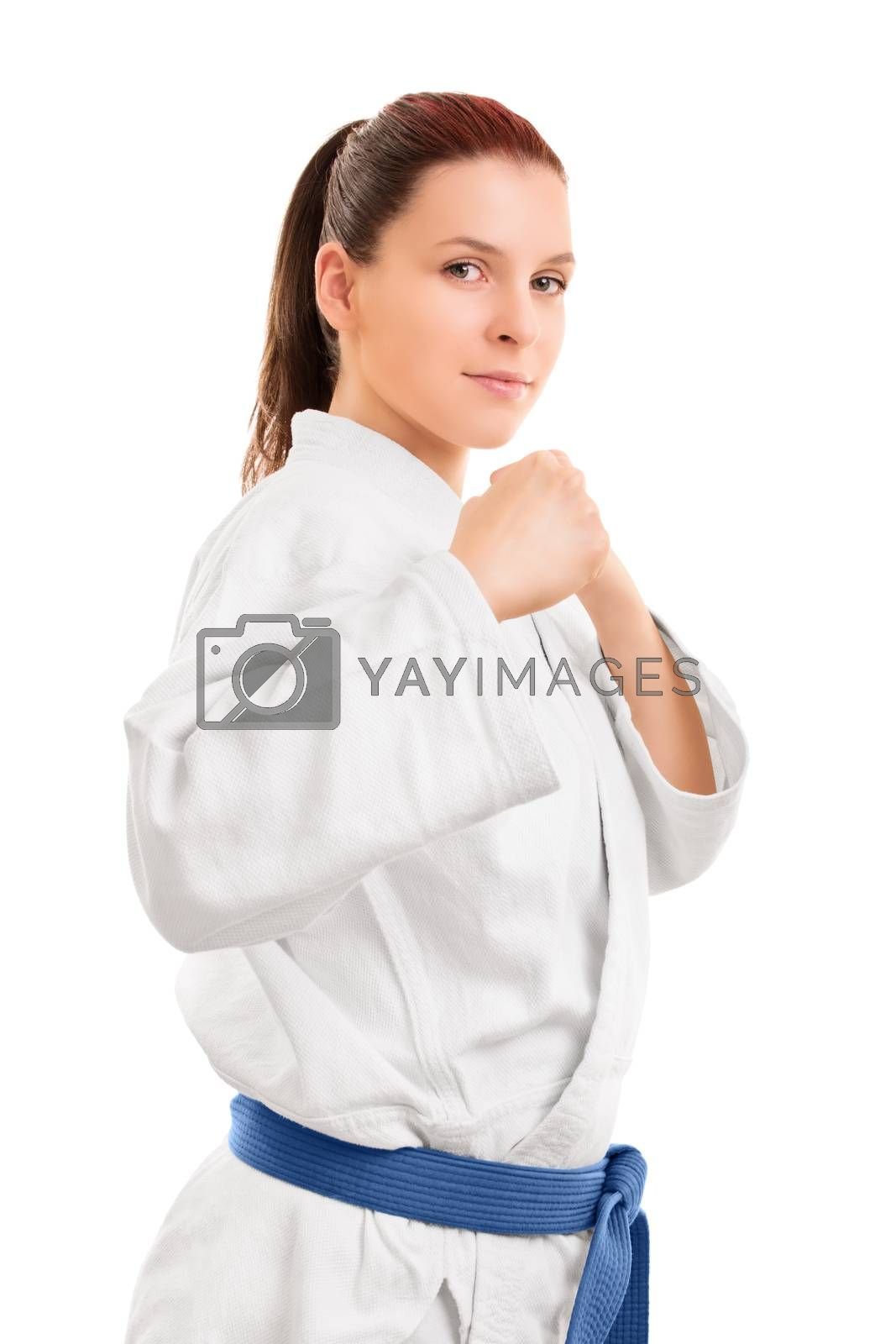 A portrait of a beautiful young girl in a kimono with blue belt standing in a combat stance, isolated on white background.