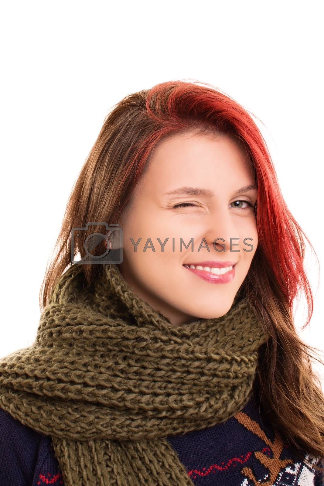 A portrait of a beautiful young girl in winter clothes, winking, isolated on white background.