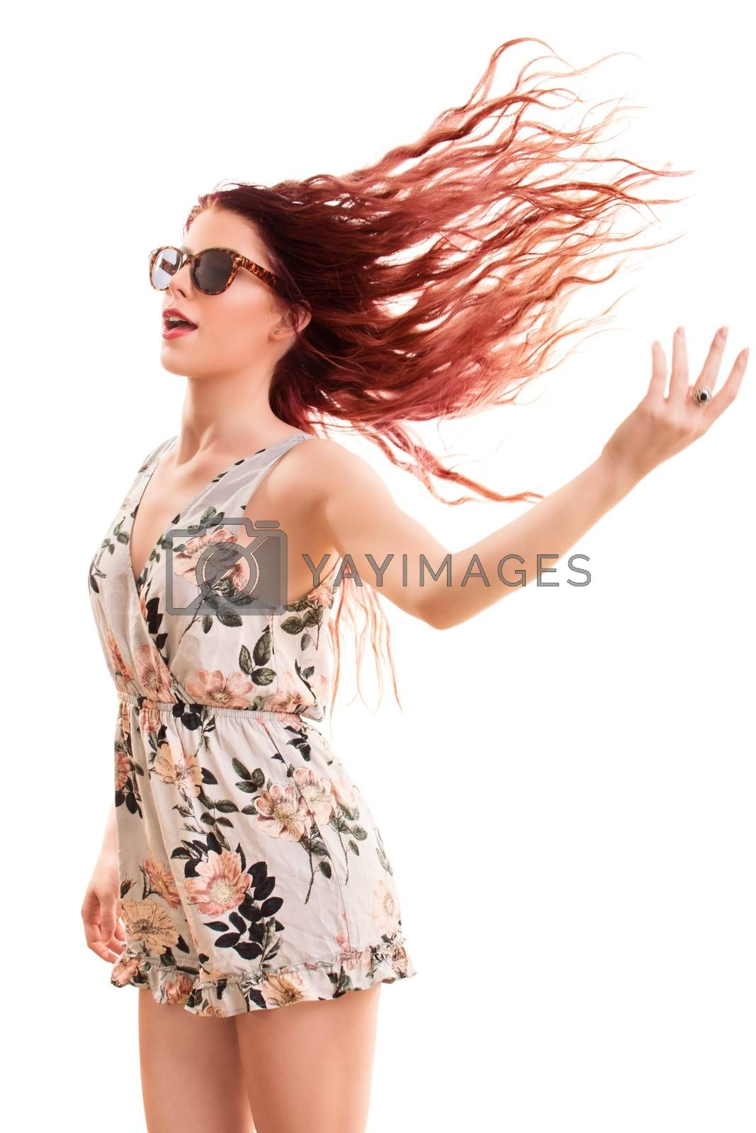 Portrait of a beautiful young girl wearing sunglasses, jumping and playing with her hair, isolated on white background.