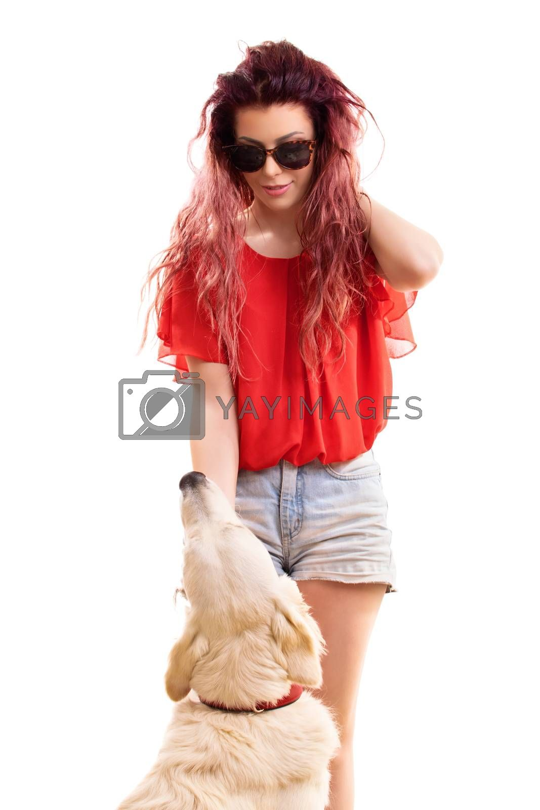Beautiful young redhead girl with sunglasses, petting her dog preparing to go out for a walk, isolated on a white background.