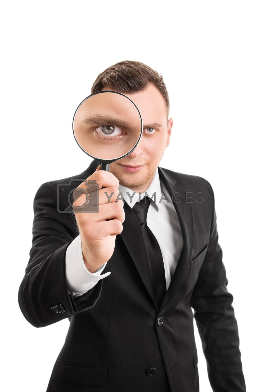 A portrait of a young businessman looking through a magnifying glass, isolated on white background.