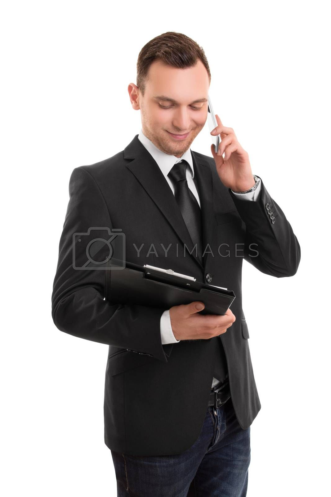 Portrait of a young businessman, holding a notepad, talking on a phone isolated on white background.