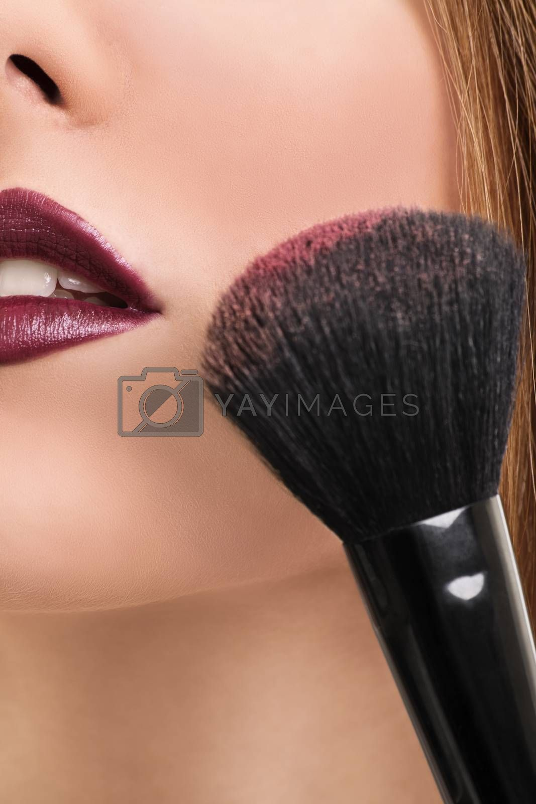 A close up shot of a girl applying make up with a make up brush.