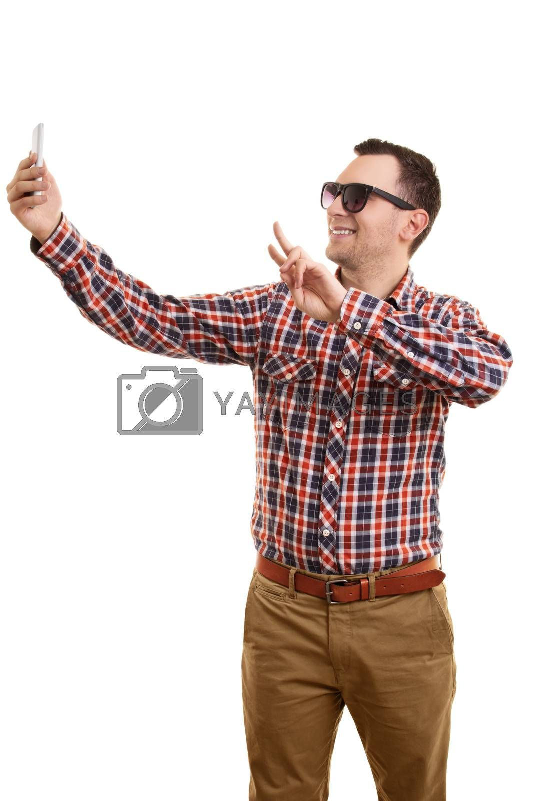 A portrait of a young fashionable man taking a selfie, isolated on white background.