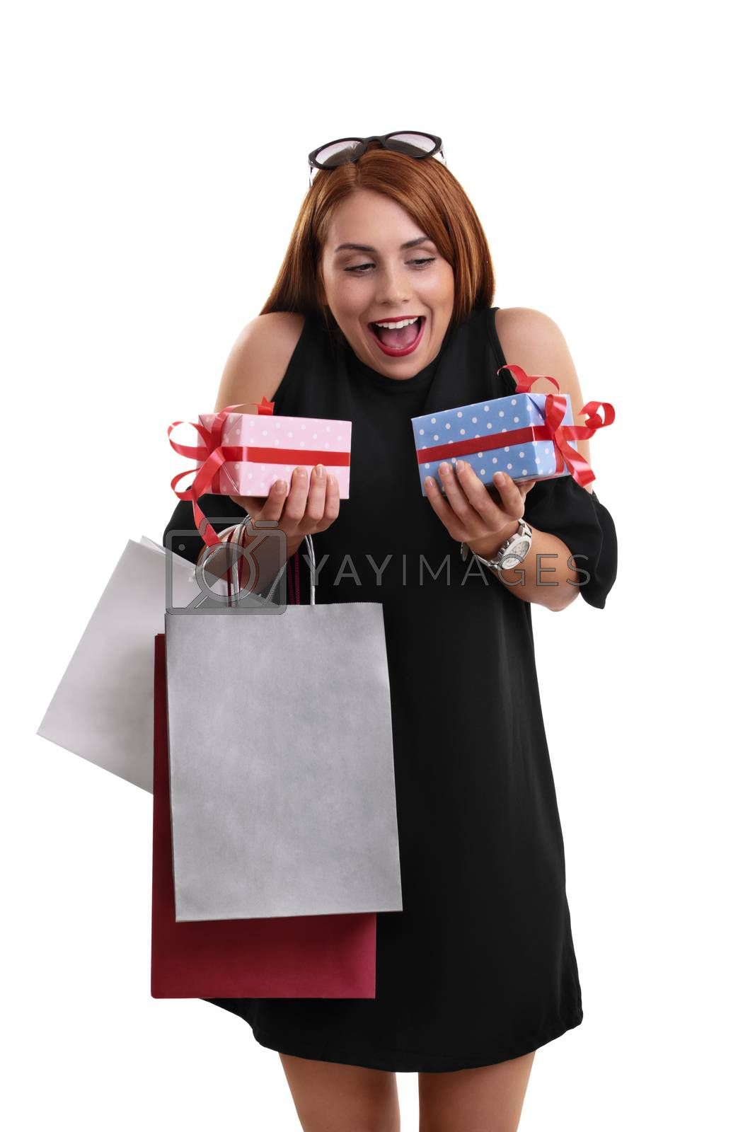 Excited beautiful young woman in a black dress holding shopping bags and presents, isolated on a white background.