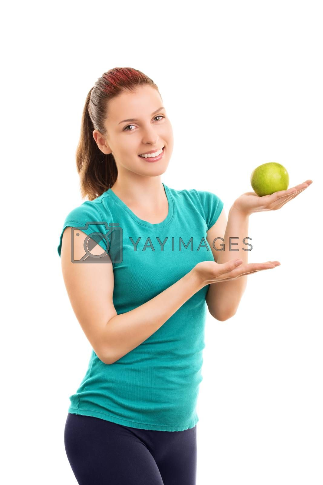 Have a bite? It's fresh and healthy. Smiling beautiful fit girl in fitness clothes holding and offering a green apple, isolated on white background.