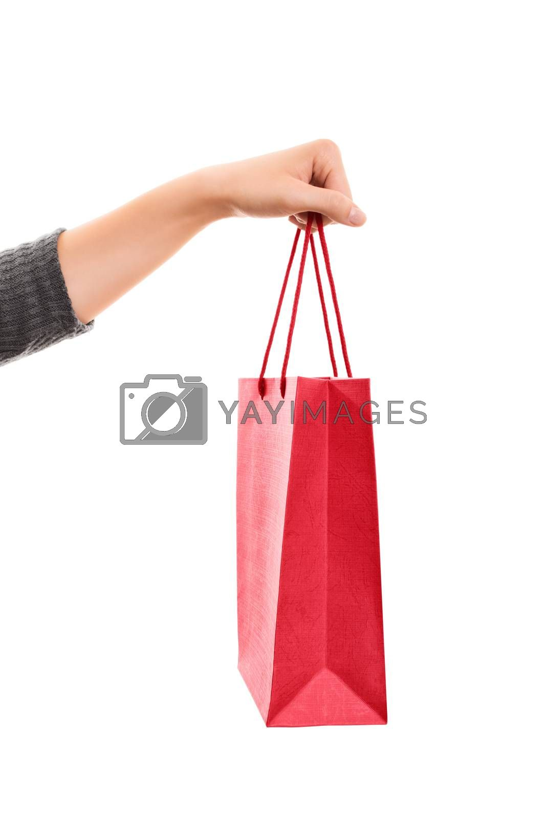 A close up shot of a female hand holding a shopping bag, isolated on white background.