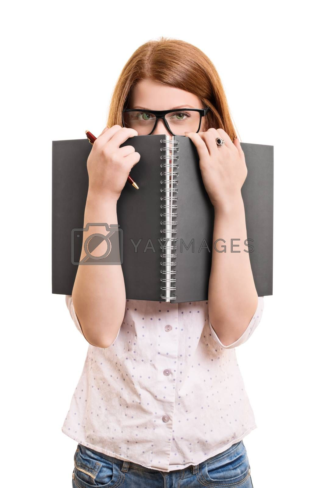 A portrait of a young female student hiding behind her book, isolated on white background.