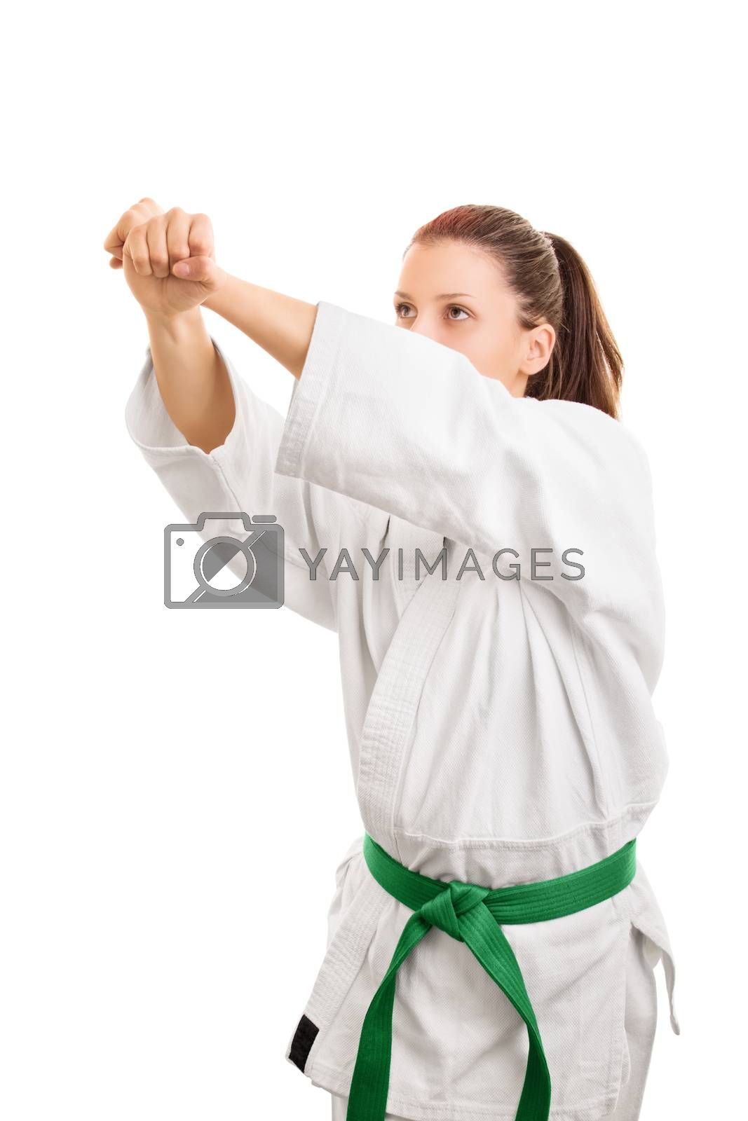 Offense-Defense. Young girl wearing kimono with green belt, practicing defense, isolated on white background.