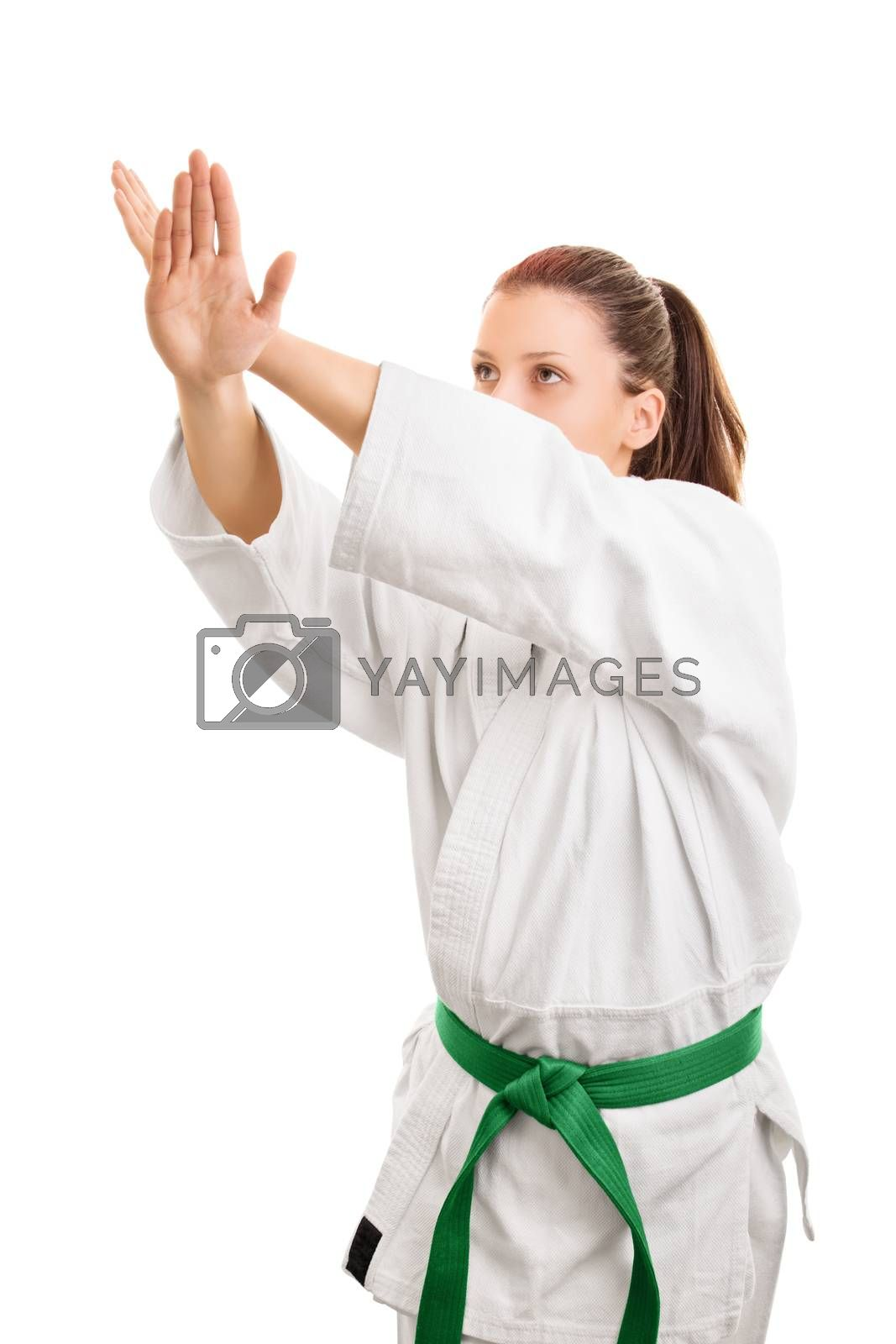 Block this way. Young girl wearing kimono with green belt in block stance, isolated on white background.