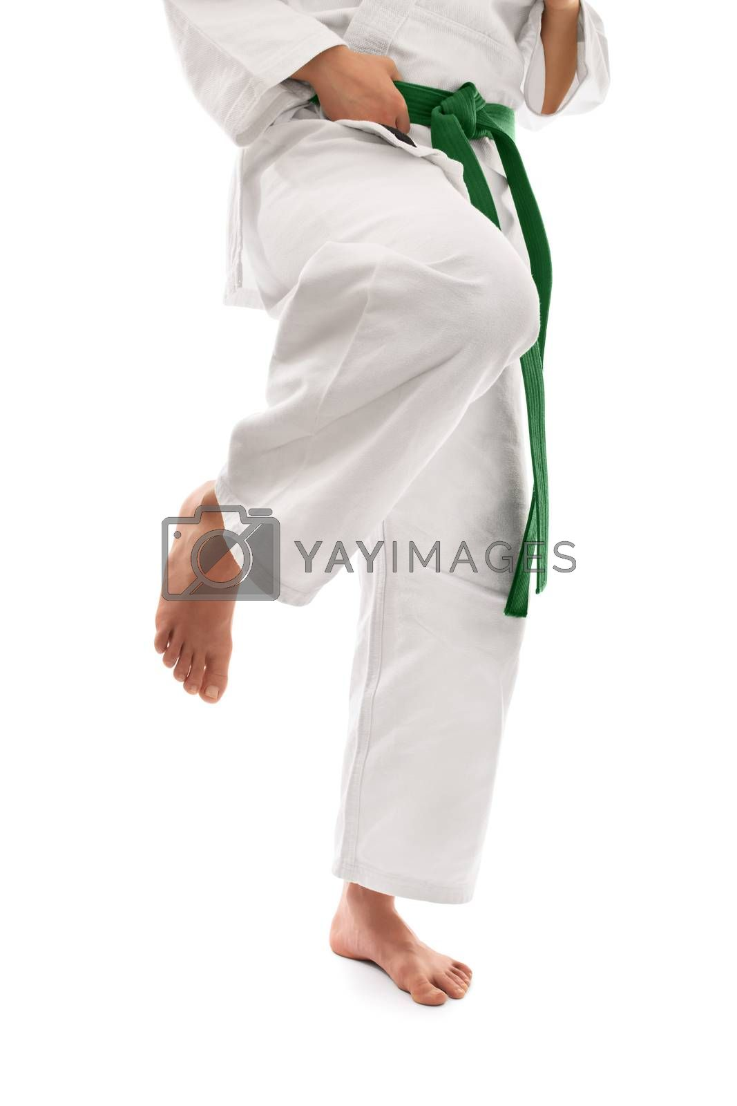 Close up shot of below the waist section of a girl in a kimono with green belt preparing for a knee kick, isolated on white background.