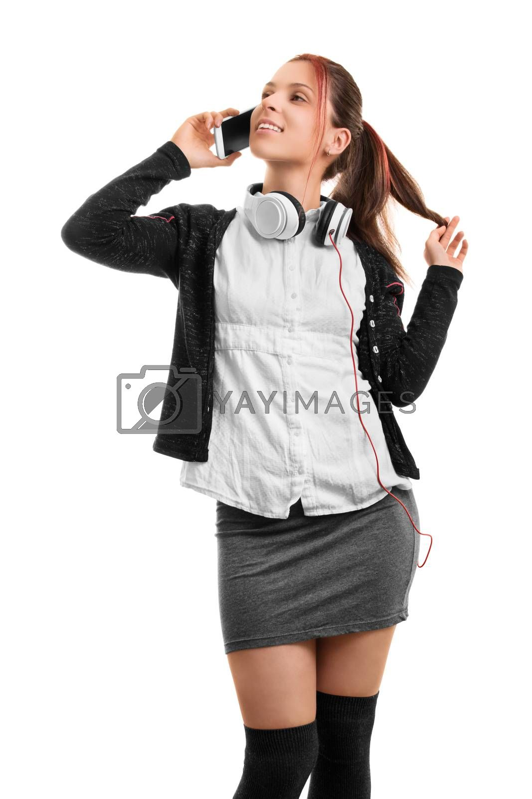 Hey, what's up? Beautiful smiling young girl in school uniform talking on the phone, isolated on white background.