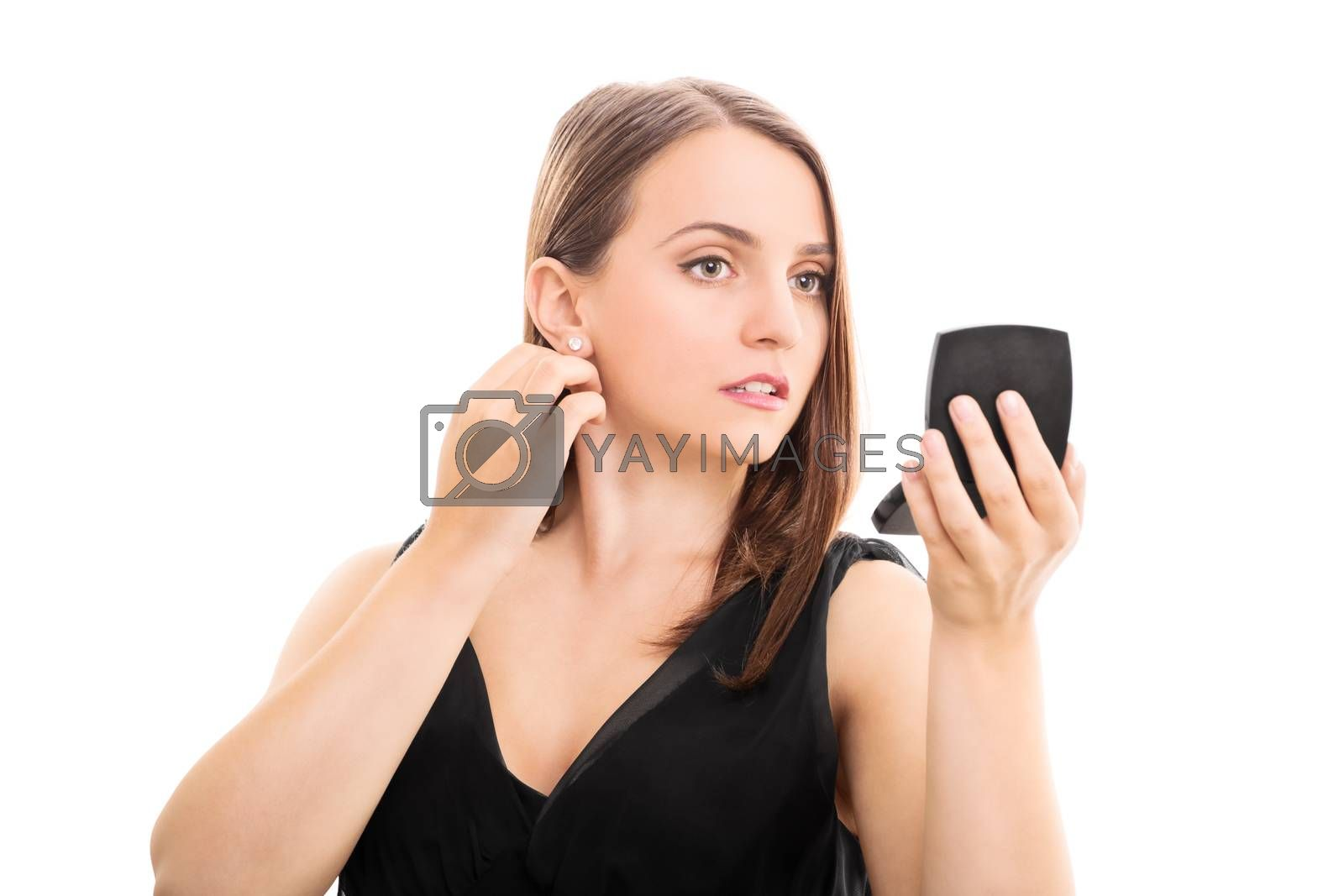Beautiful elegant young woman looking in a makeup mirror, isolated on white background. Young woman preparing for a date.
