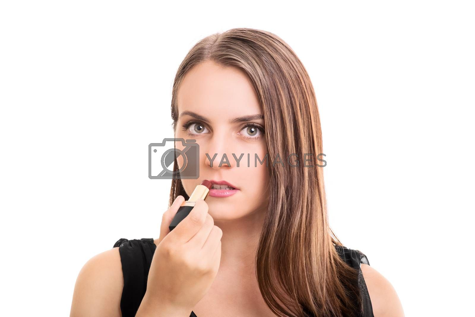 Beautiful elegant young woman putting on a lipstick, isolated on white background.