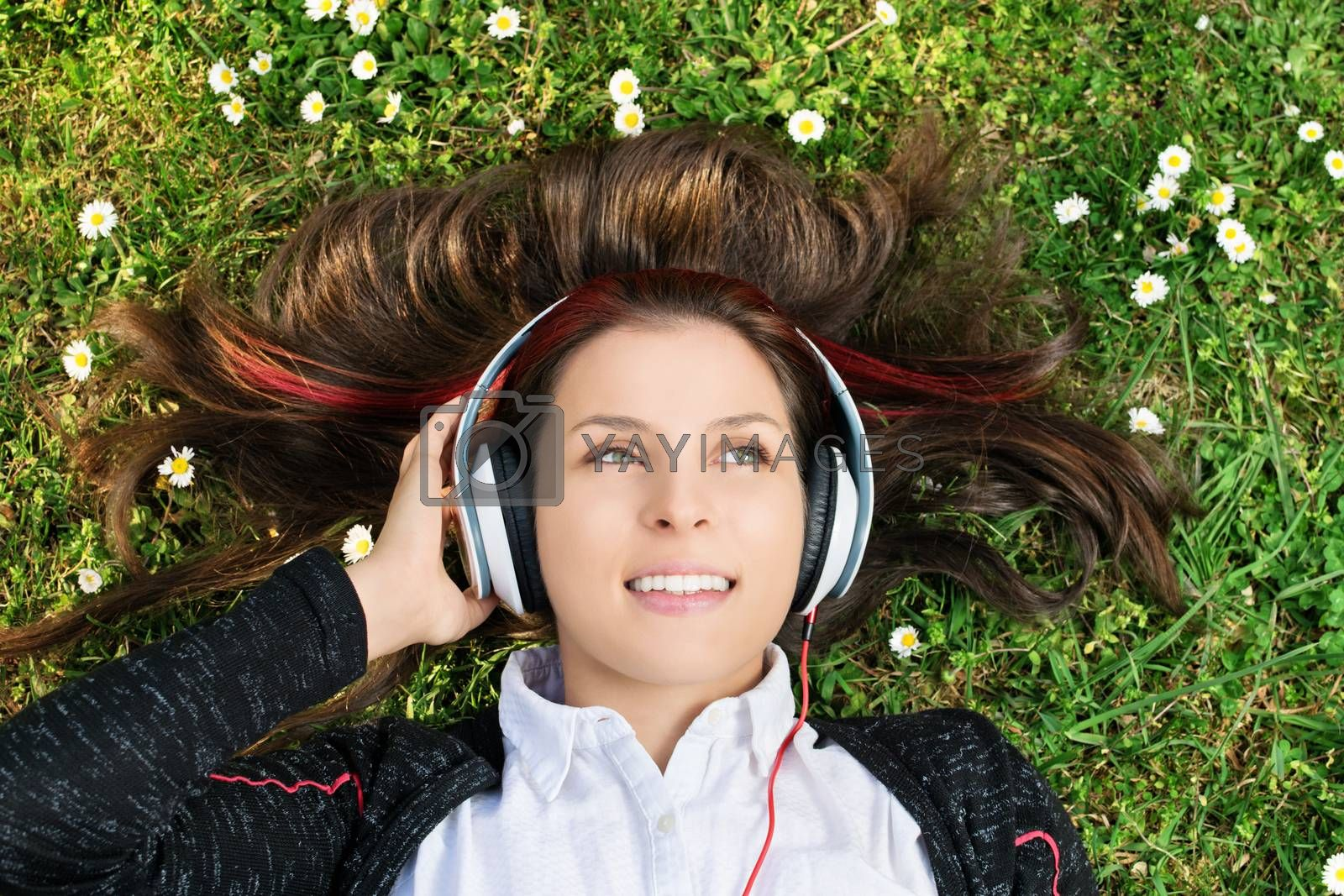 A close up portrait of a beautiful young girl lying on the grass in a park, listening to music on her headphones.