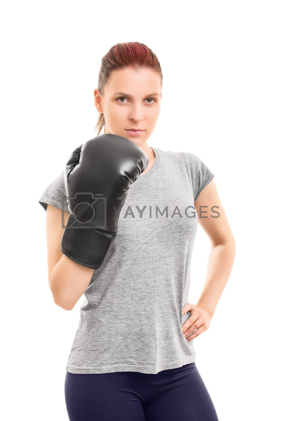 A portrait of a beautiful young girl posing with a boxing glove, isolated on white background.