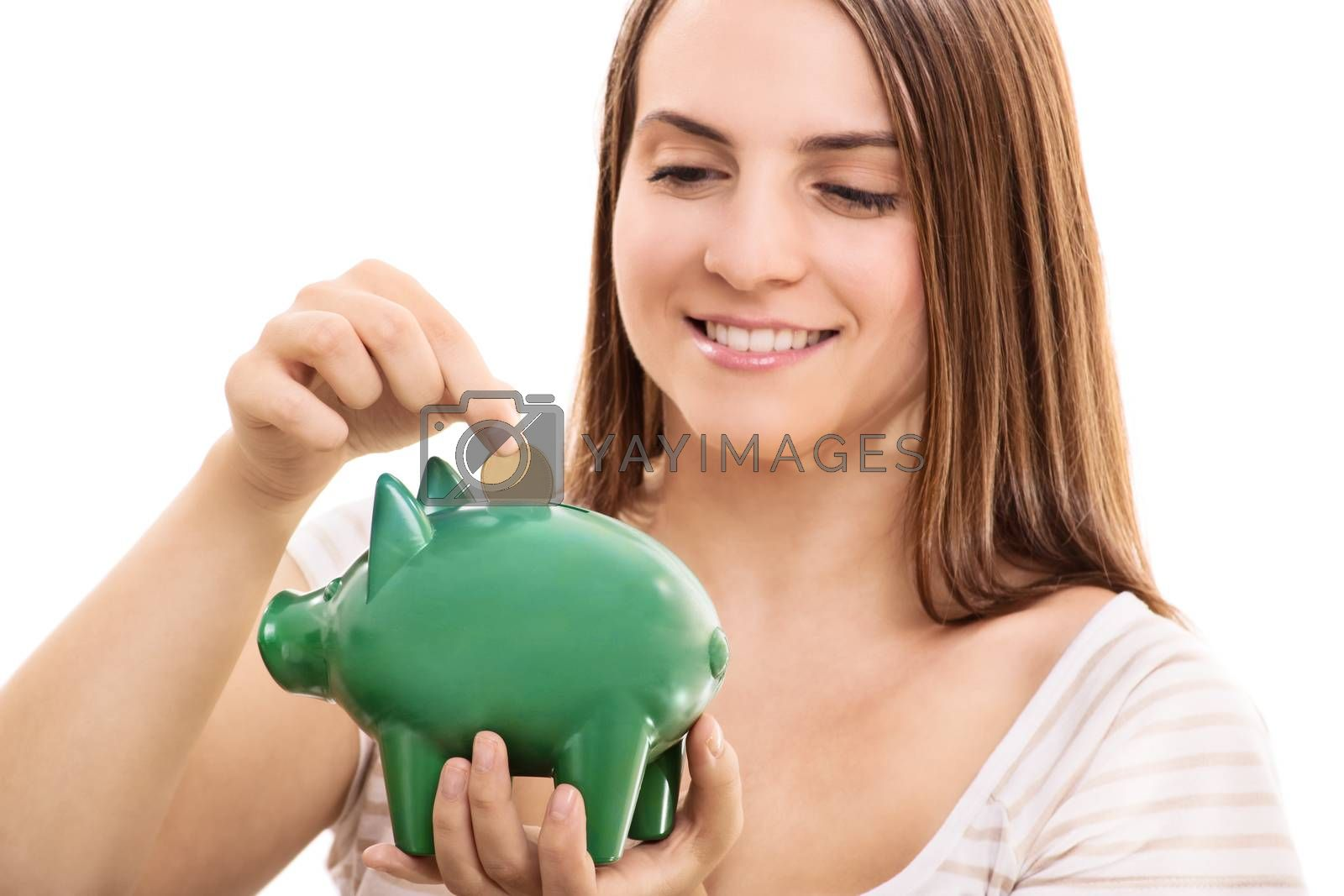 Young girl putting money in a piggy bank, isolated on white background.
