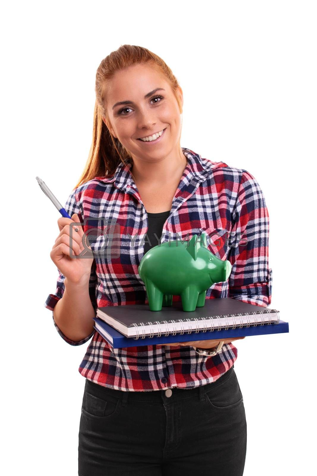 Smiling young student holding a green piggy bank on a stack of books, pointing with a pen, isolated on white background.