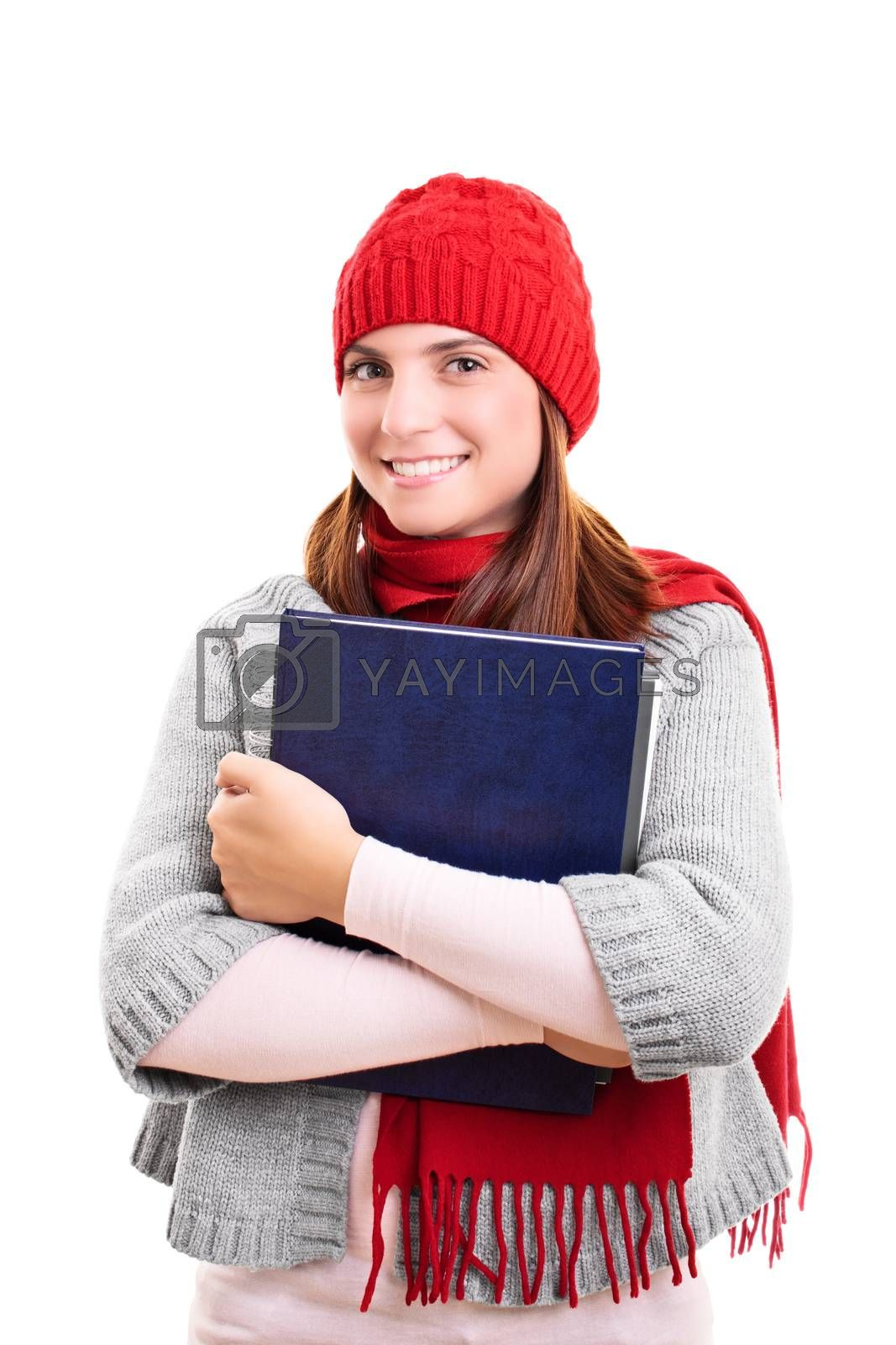 Portrait of a beautiful smiling female student in winter clothes holding a book, isolated on white background. I'm ready for winter exam season.