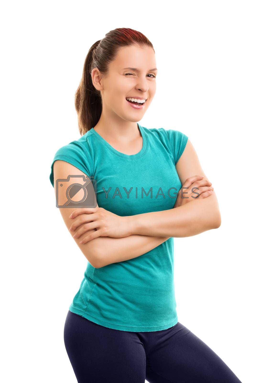 Body, mind and spirit all focused in good health. Smiling young athlete winking, isolated on white background.