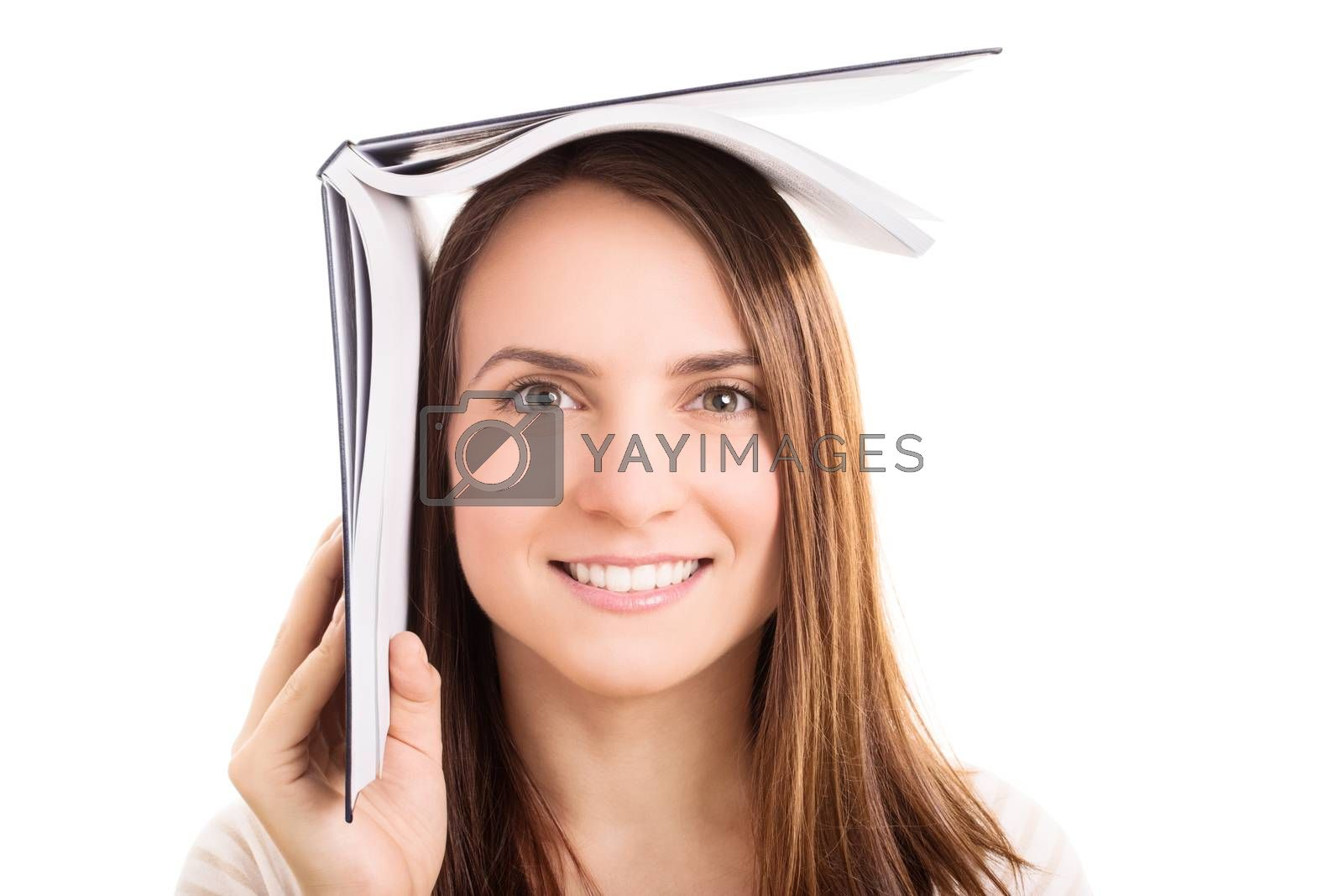 Young girl holding a book on top of her head, isolated on white background. I'm hiding from the exams.