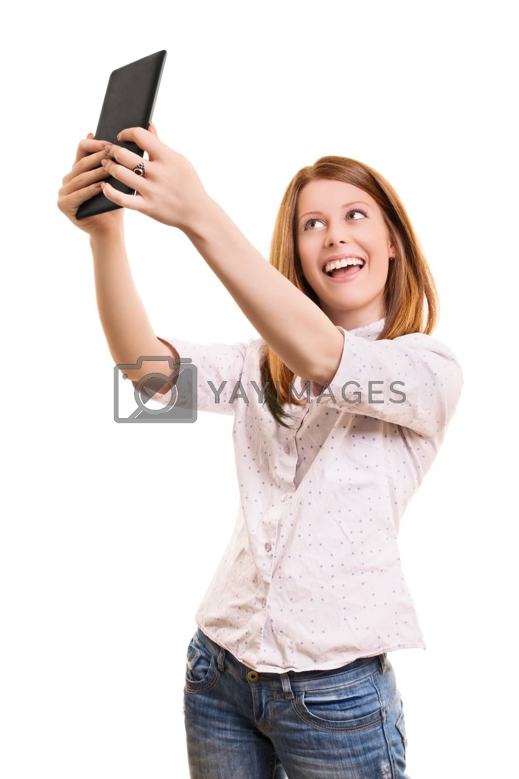 A portrait of a young beautiful girl taking a selfie with her tablet, isolated on white background.
