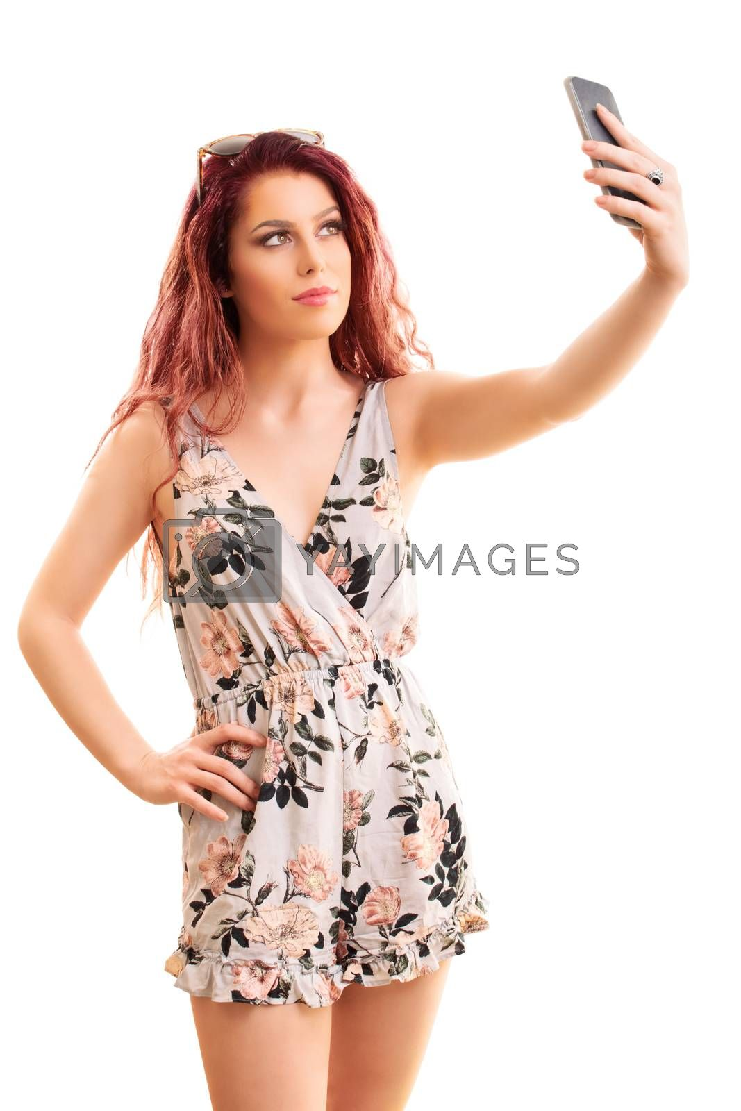 Beautiful smiling fashionable young girl taking a selfie, isolated on a white background.