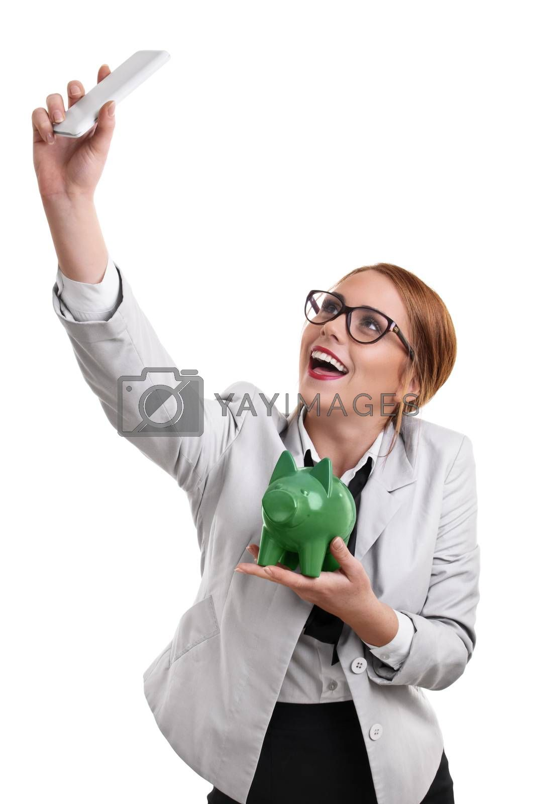 Smiling beautiful young business woman dressed in a suit with glasses taking a selfie with a green piggy bank, isolated on a white background.