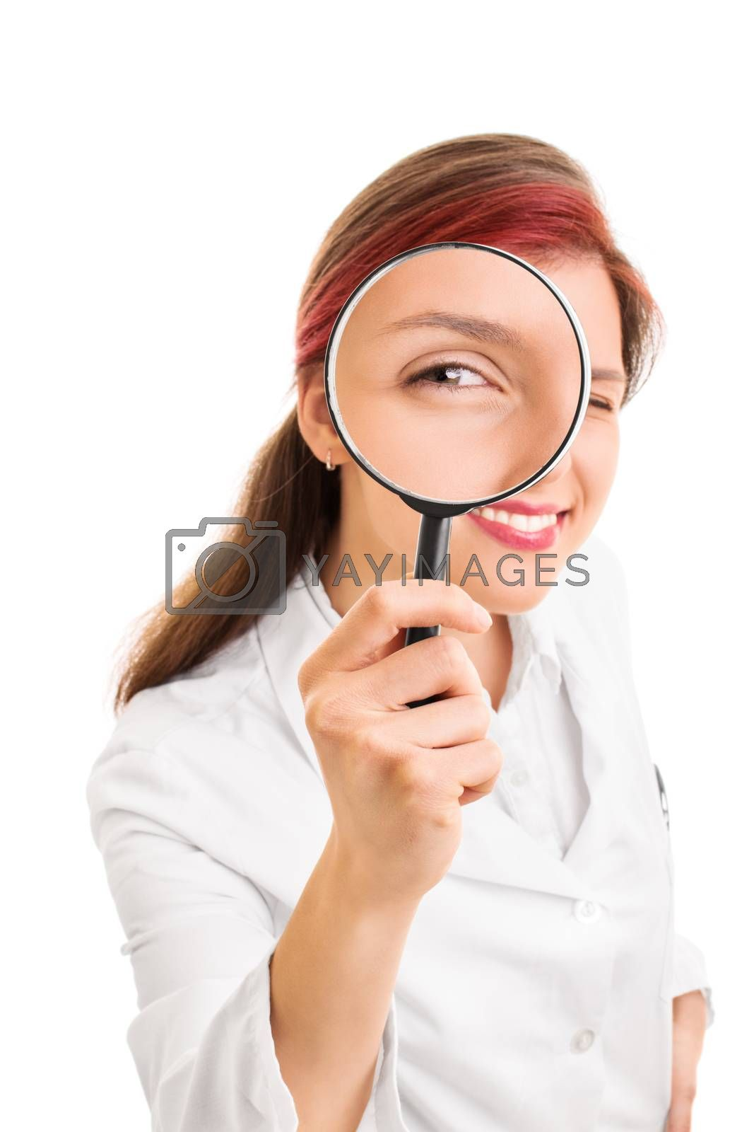 Let me take a look at you. Close up shot of a beautiful smiling young doctor looking though a magnifying glass, isolated on white background.