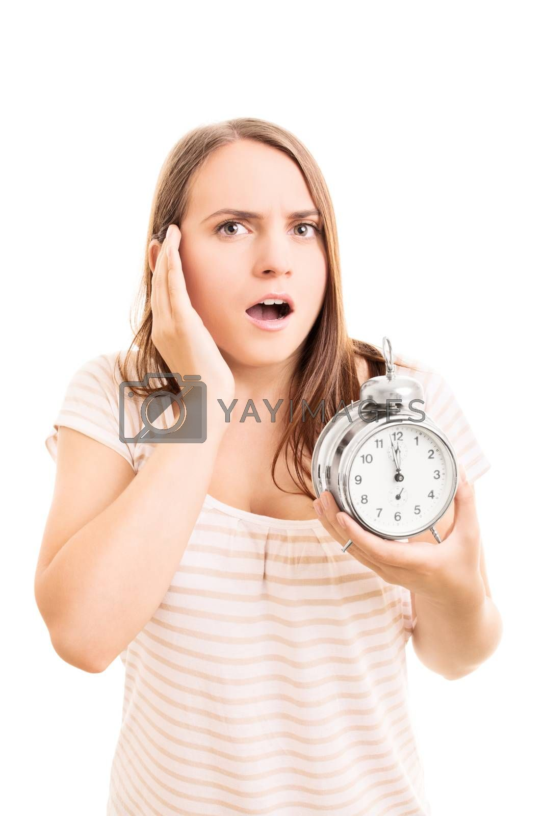 Portrait of a beautiful young woman holding an alarm clock, leaving an impression she's late for something, isolated on white background.