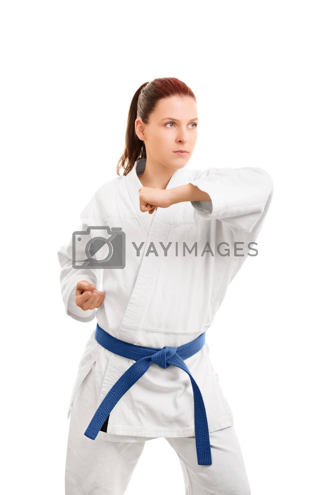 A portrait of a young girl in a kimono with blue belt demonstrating a blocking technique, isolated on white background.
