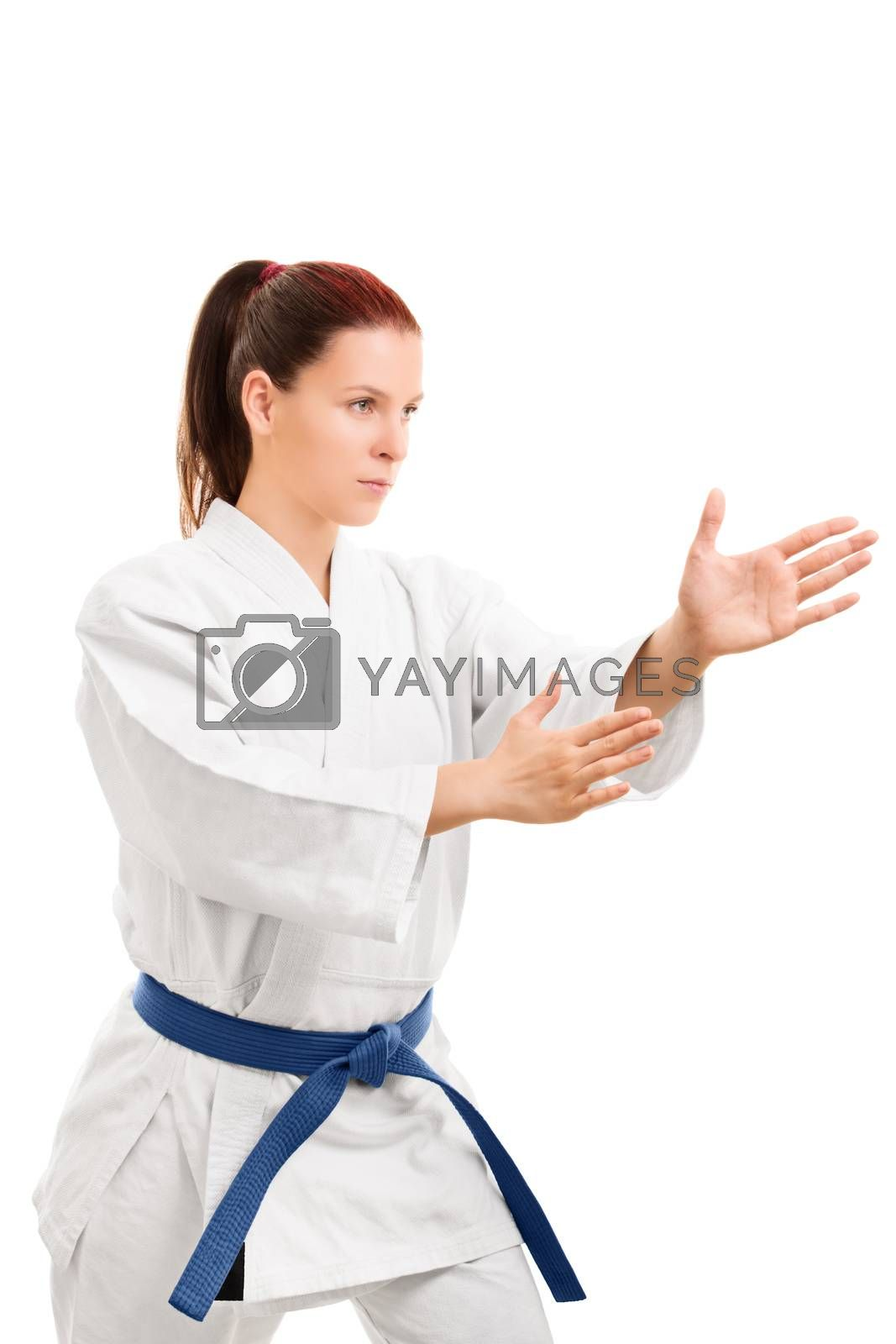 A portrait of a young girl in a kimono with blue belt in a fighting stance, isolated on white background.