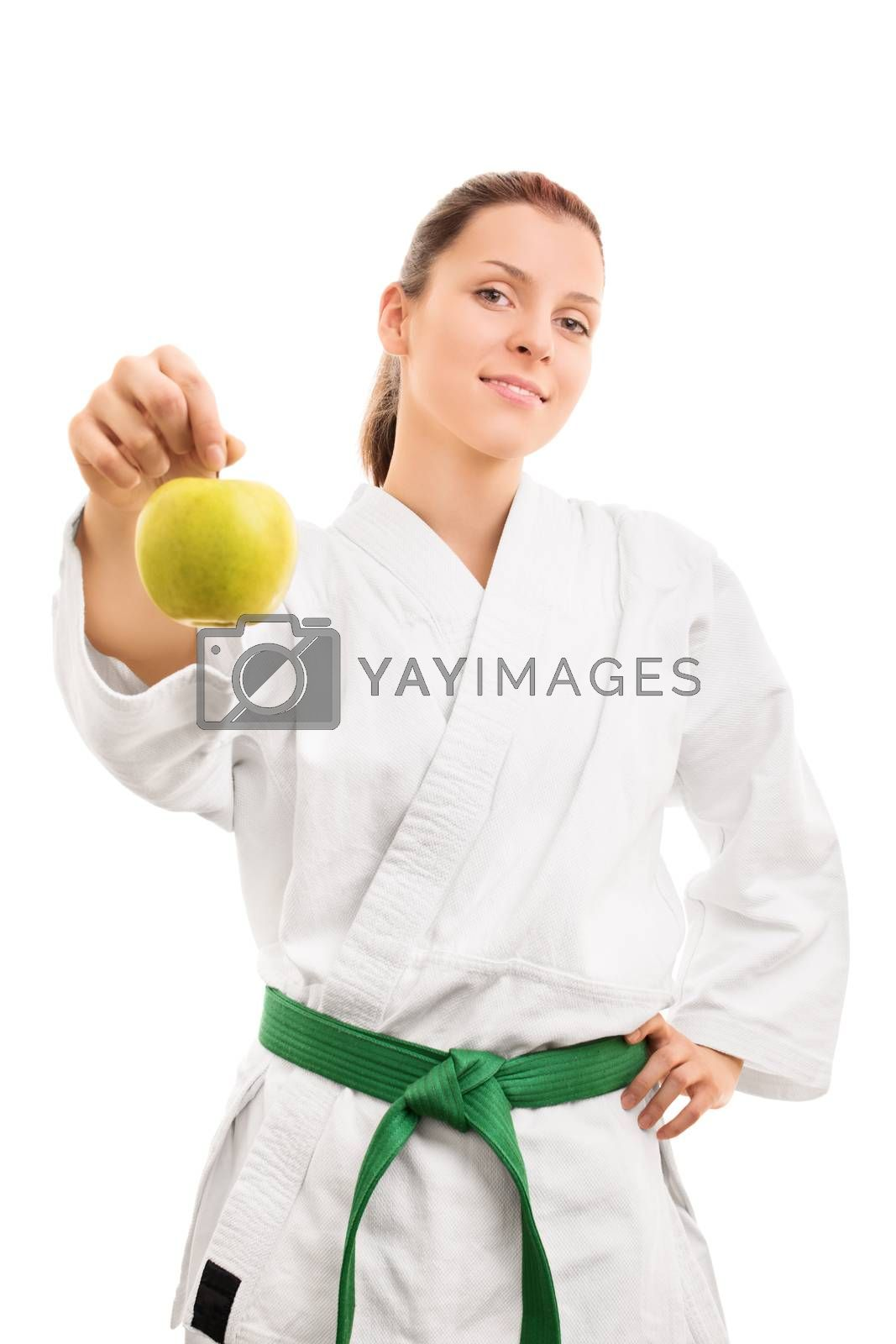 Sports and healthy eating. Beautiful smiling young girl in kimono with green belt offering an apple, isolated on white background.