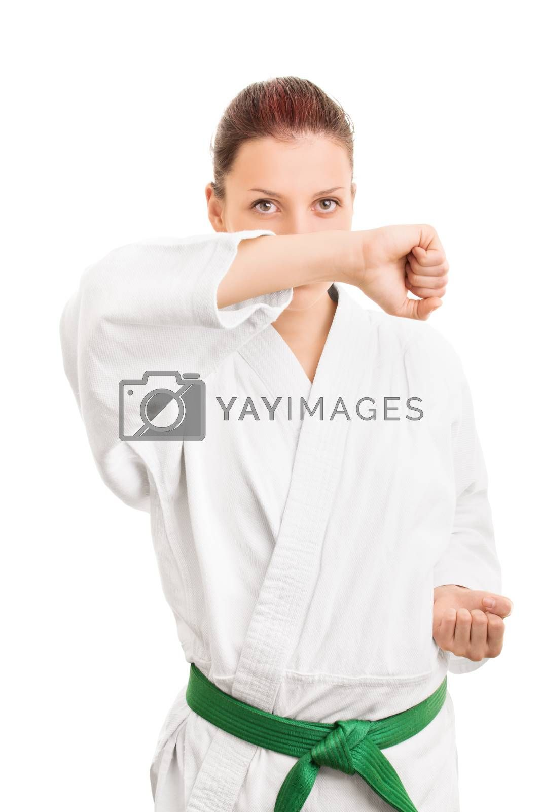 Young girl in kimono with green belt making a block, isolated on white background.