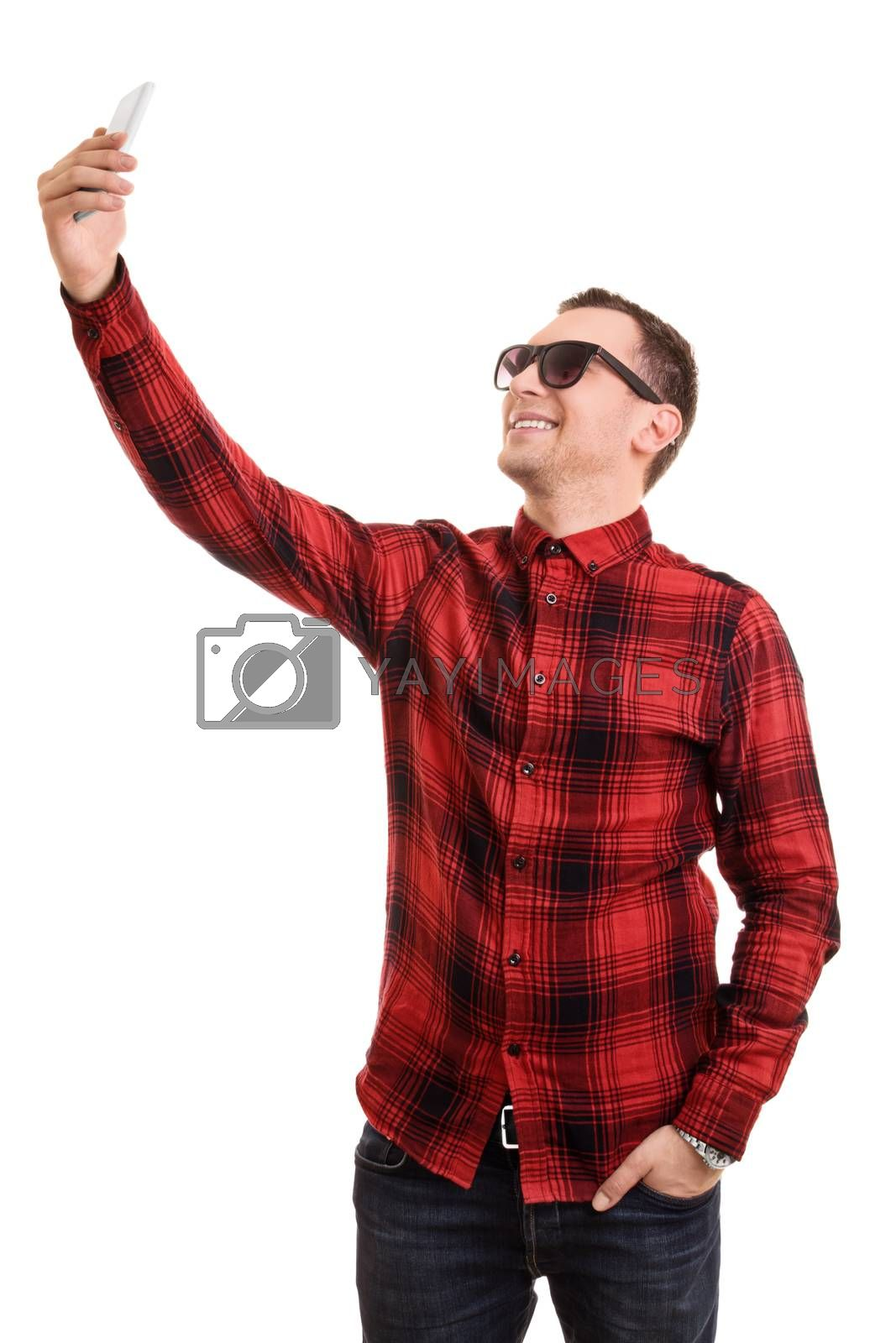 A portrait of a fashionable young man taking a selfie, isolated on white background.
