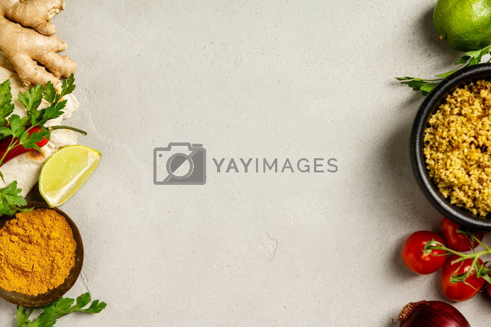 Couscous, naan bread, green leaf and cooking ingredients on concrete background. Flat lay. Healthy vegetarian food and cooking concept