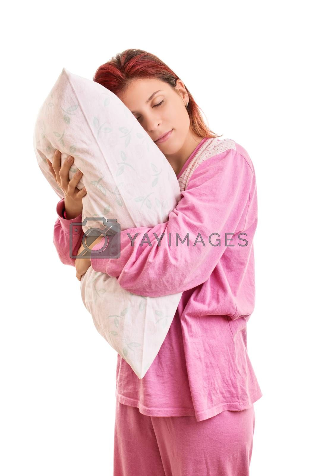 My comfortable pillow. Beautiful young girl in pink pajamas with closed eyes hugging a pillow, isolated on white background.
