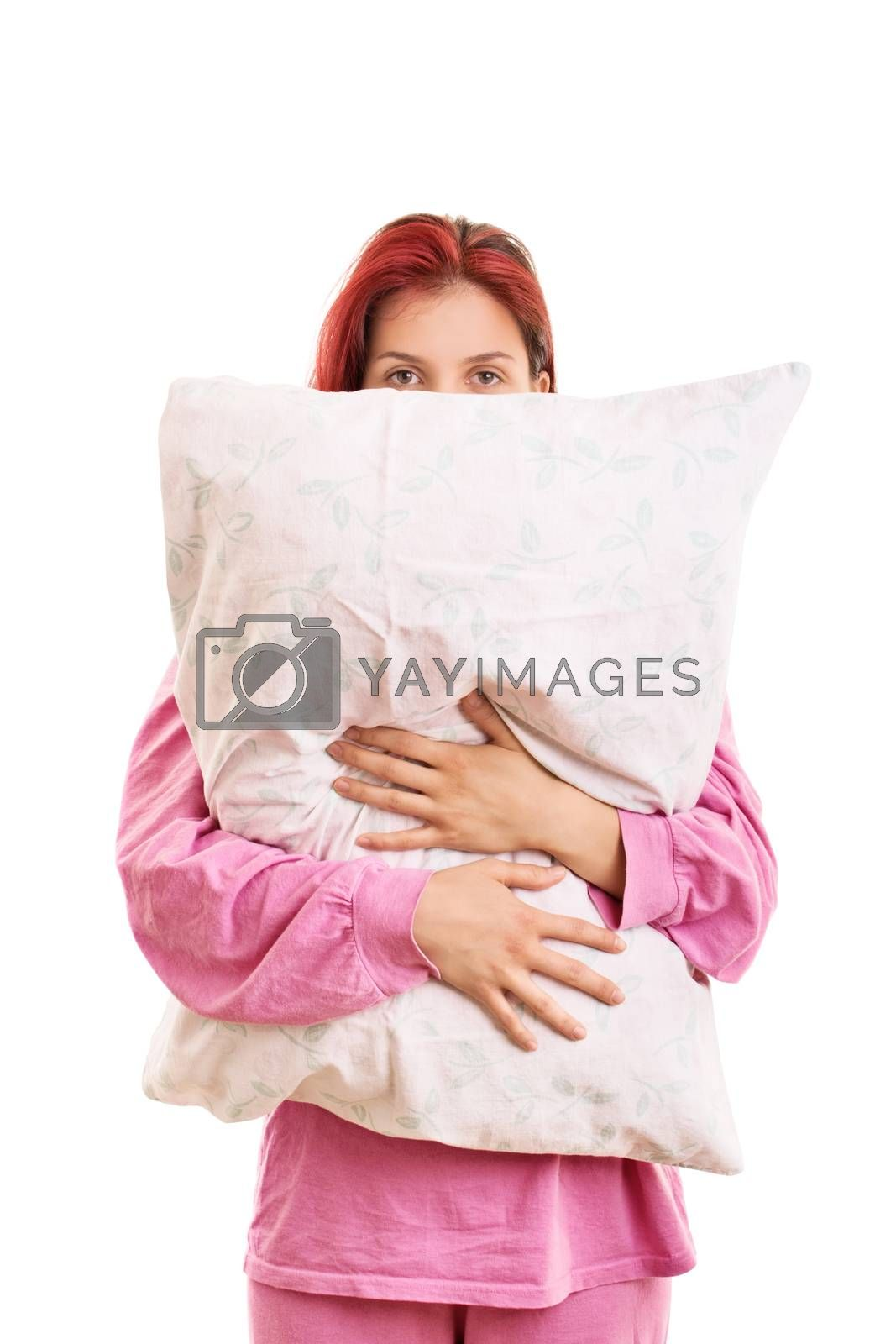 Hiding from the insomnia behind my pillow. Tired and sleepy young girl in pink pajamas hugging a pillow, isolated on white background.