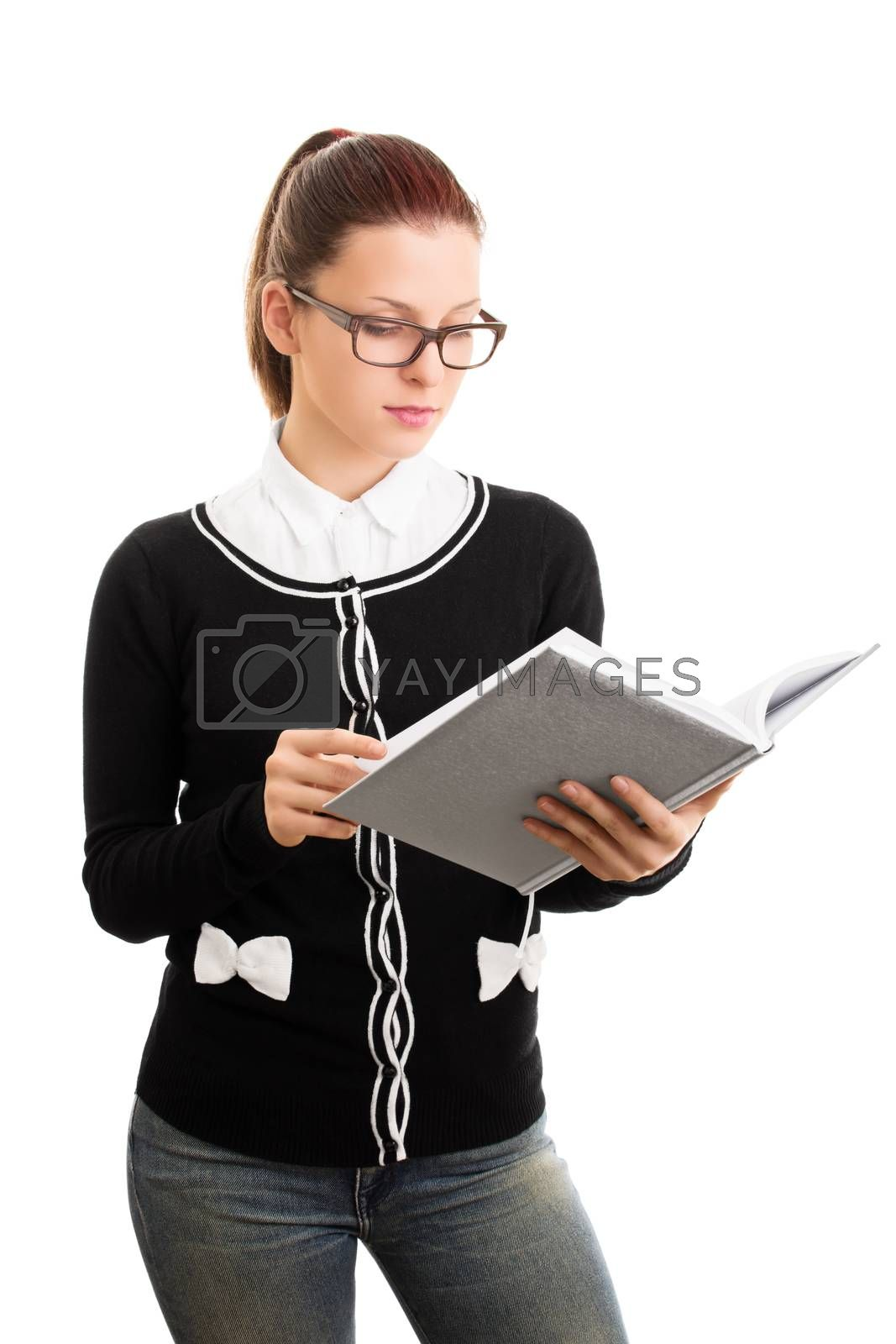 Reviewing notes. Reading something. Beautiful young student girl with glasses looking at an open notebook, isolated on white background.